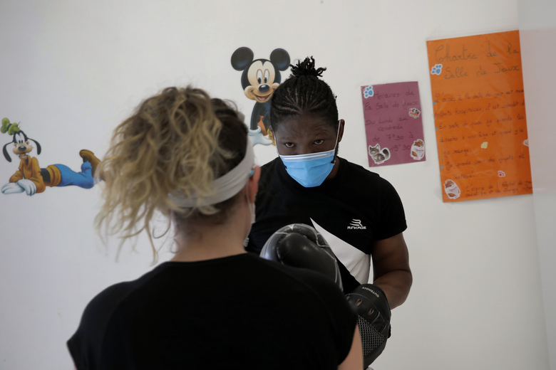 In this Wednesday, May 27, 2020 photo, Marina, a medical worker, boxes during a training session with French boxer Hassan N'Dam, at the Villeneuve-Saint-Georges hospital, outside Paris. A world champion French boxer is taking his skills to hospitals, coaching staff to thank the medical profession for saving his father-in-law from the virus, and giving them new confidence and relief from their stressful jobs. (AP Photo/Christophe Ena)