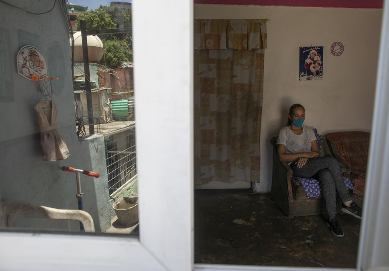 In this April 24, 2020 photo, Maylin Perez sits inside her three-room apartment in Caracas, Venezuela. Perez said she tries to convince her son who is working in Peru not to worry about sending money because she's more concerned about him potentially getting infected with the new coronavirus. (AP Photo/Ariana Cubillos)