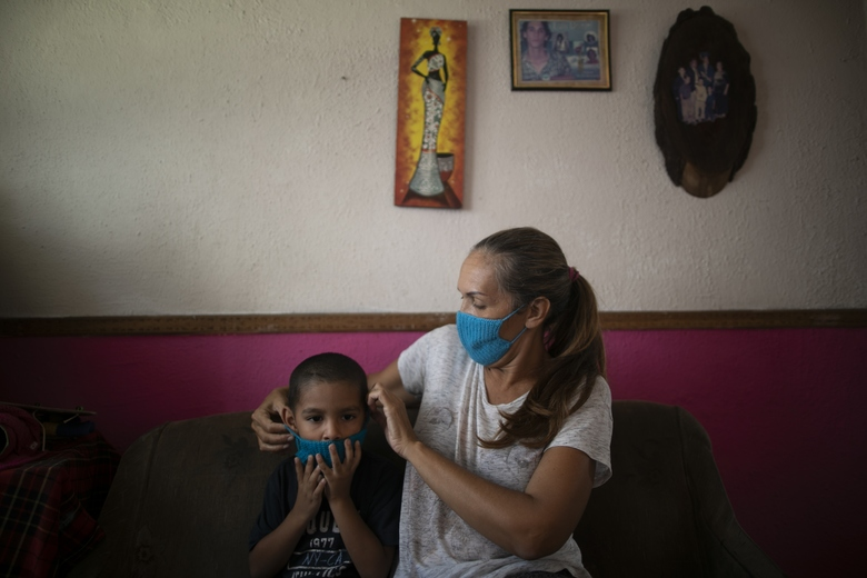 In this April 24, 2020 photo, Maylin Perez who says the potential spread of the new coronavirus virus weighs on her heavily, puts a knitted face mask on her grandson Daniel Cocho, in their apartment in Caracas, Venezuela. Perez knits the colorful face masks to barter for extras besides the lentils and rice she receives from a monthly, government subsidized box of food. (AP Photo/Ariana Cubillos)