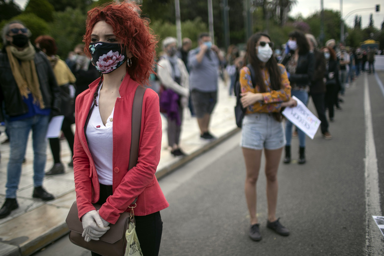 Artists, wearing masks to protect against the spread of the coronavirus, protest outside the Greek parliament in central Athens, on Thursday May 7, 2020. Associations representing musicians, artists and performers want the government to expand income support schemes as they face a tourism season hit by the pandemic. (AP Photo/Petros Giannakouris)