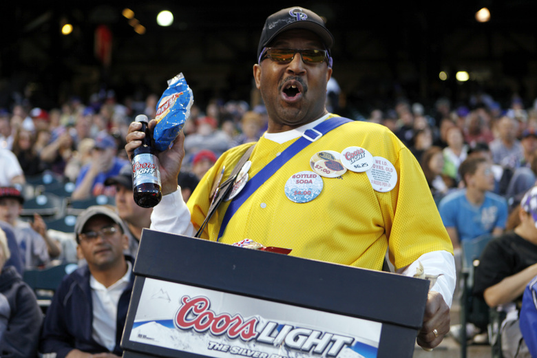 FILE – In this May 9, 2011, file photo, a vendor sells beer and peanuts at a Colorado Rockies baseball game at Coors Field in Denver. As sports have begun to return around the world, the only thing that even comes close to normalcy is happening on the field. For the fans, team owners, sponsors and just about everyone else associated with college and professional sports, the coronavirus pandemic has forced changes both big and small. (AP Photo/Ed Andrieski, File)