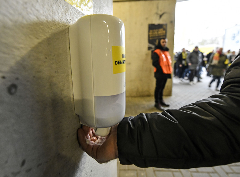 "FILE – In this Feb. 29, 2020, file photo, a fan washes his hands at a new disinfection station in the stadium prior the German Bundesliga soccer match between Borussia Dortmund and SC Freiburg in Dortmund, Germany. ""In large masses, there is no system that can effectively prevent another person from giving germs to a second individual,"" said Philip Tierno, a clinical professor of pathology at New York University's Grossman School of Medicine. (AP Photo/Martin Meissner, File)"