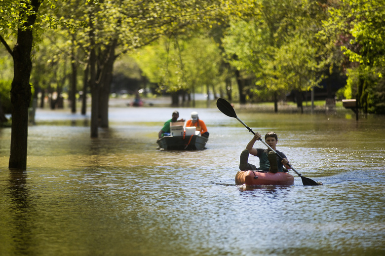 Hunter Klich, 14, maneuvers a kayak down the middle of Walden Woods Drive, Wednesday, May 20, 2020, in Midland, Mich., as residents coped with flooding. (Katy Kildee/Midland Daily News via AP)