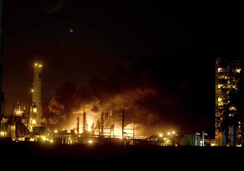 FILE – In this Wednesday, Nov. 27, 2019, file photo, flames and thick, black smoke light up the pre-dawn sky following and explosion at the TPC plant in Port Neches, Texas. The Occupational Safety and Health Administration said that it cited TPC for three willful violations by not developing and implementing procedures for emergency shutdown and not inspecting and testing process vessel and piping components. TPC faces $514,692 in civil OSHA fines, stemming from the explosion and fires. (Kim Brent/The Beaumont Enterprise via AP)
