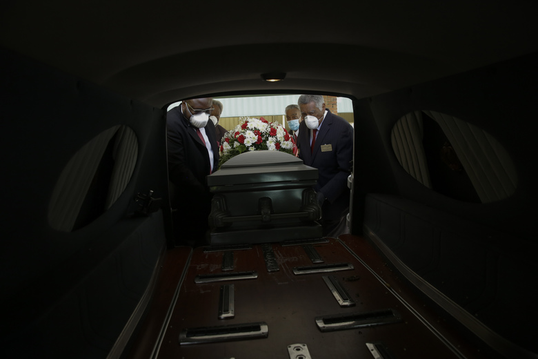 Mortician Cordarial O. Holloway, foreground left, funeral director Robert L. Albritten, foreground right, and funeral attendants Eddie Keith, background left, and Ronald Costello place a casket into a hearse on April 18, 2020, in Dawson, Ga. Across the county, the latest Associated Press analysis of available state and local data shows that nearly one-third of those who have died are African American, with black people representing about 14% of the population in the areas covered. (AP Photo/Brynn Anderson)