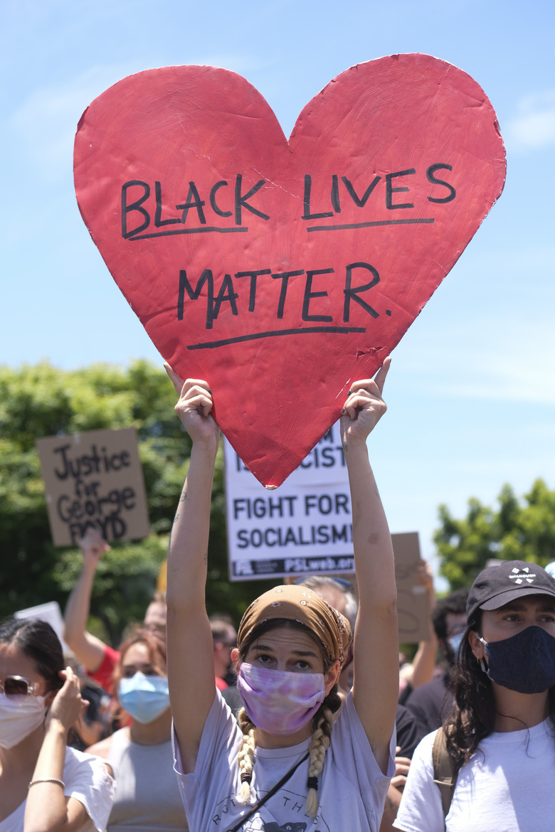 A protester holds a sign during a protest in Los Angeles, Saturday, May 30, 2020. Demonstrators took to the streets of Los Angeles to protest the death of George Floyd, a black man who was killed in police custody in Minneapolis on May 25. (AP Photo/Ringo H.W. Chiu)