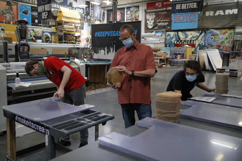 From left, Patrick Bergmann, Scott Proctor and Logan Perdelwitz prepare acrylic barriers for delivery to a casino at Screaming Images, Wednesday, May 13, 2020, in Las Vegas.The company primarily designed, printed and installed large format signs for sporting and other events, but has started to make acrylic barriers for casinos and other business to use to protect workers and patrons from the spread of the coronavirus. (AP Photo/John Locher)
