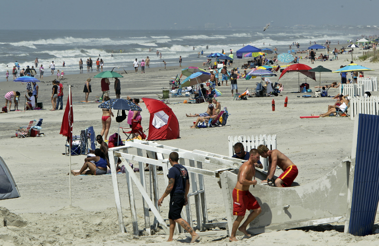 CORRECTS FOR CLARIFICATION- In this July 4, 2014 file photo, bathers crowd the beach in Atlantic Beach, N.C. Atlantic Beach was among the towns that once tried to block outsiders from using its beaches, but has since changed the policy. When it reopens in mid-May 2020, only residents of New Jersey's Point Pleasant Beach would be able to use the Point Pleasant Beach. New Jersey Gov. Phil Murphy said reopening public beaches is a local decision. But in doing so, he said, the entire public has to be allowed on the sand. (Chris Seward/The News & Observer via AP, File)