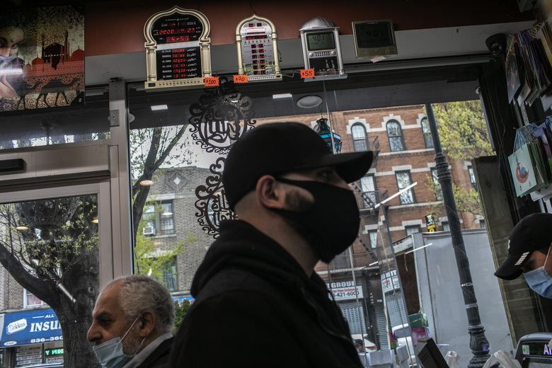 Mohammed Widdi, 31, coordinator of Muslims Giving Back waits at the cashier counter while on a grocery run for a family affected by COVID-19 in the Bay Ridge neighborhood of Brooklyn, New York, on Monday, April 27, 2020. (AP Photo/Wong Maye-E)