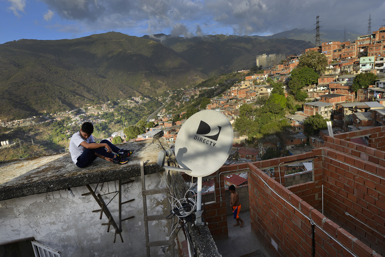 FILE – In this  Jan. 9, 2020 file photo, a DirectTV dish stands on home in the Catia neighborhood of Caracas, Venezuela. AT&T, one of the last major American companies still operating in Venezuela, said Tuesday, May 19, 2020 it will immediately abandon Venezuela's pay TV market, as U.S. sanctions prohibit its DirecTV platform from broadcasting channels that it is required to carry by the Venezuelan government, making it impossible to comply with the legal requirements of both countries. (AP Photo/Matias Delacroix, File)