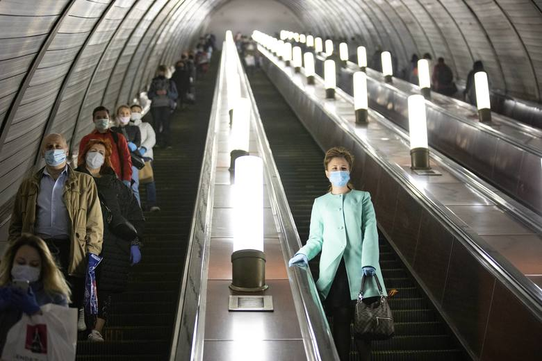 People wearing face masks and gloves to protect against coronavirus, observe social distancing guidelines as they go down the subway on the escalator in Moscow, Russia, Tuesday, May 12, 2020. From Tuesday onward, wearing face masks and latex gloves is mandatory for people using Moscow's public transport. President Vladimir Putin on Monday declared an end to a partial economic shutdown across Russia due to the coronavirus pandemic, but he said that many restrictions will remain in place. (AP Photo/Alexander Zemlianichenko)