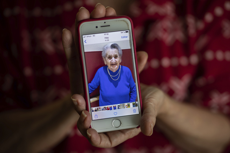 In this Monday, May 18, 2020 photo, Isabel Fraile shows a picture of her mother Estefania Carretero, 93, in Madrid, Spain. Estefania Carretero was one of the residents at the Usera Center for the Elderly, who died during the coronavirus outbreak in Spain. More than 19,000 coronavirus deaths in Spain's nursing homes have prompted a re-examination of a system. (AP Photo/Bernat Armangue)