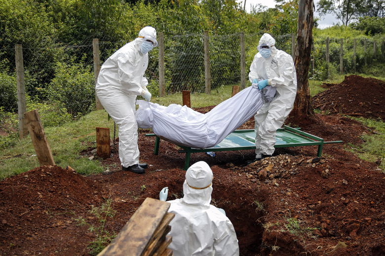 """Members of a team dedicated to burying Muslim victims of the new coronavirus bury Mohamed Ali Hassan, whose cousin said had been unaware he had the new coronavirus and died in his house in the Eastleigh area, at the Langata Muslim cemetery in Nairobi, Kenya Thursday, May 7, 2020. The Kenyan government on Wednesday sealed off the Eastleigh area of the capital Nairobi and the Old Town area of the port city of Mombasa, with no movement permitted in or out for 15 days, due to """"a surge in the number of positive coronavirus cases"""". (AP Photo/Brian Inganga)"""
