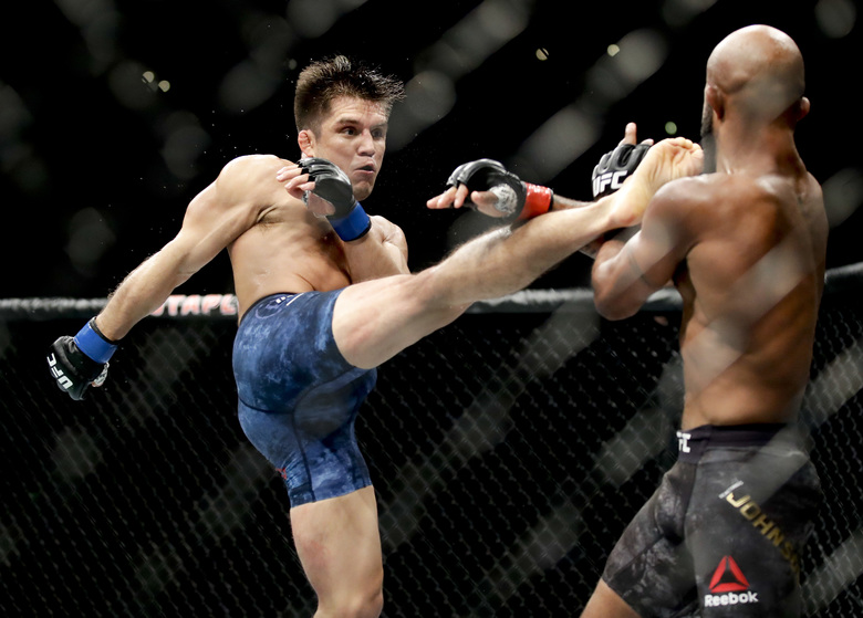 FILE – In this Aug. 4, 2018, file photo, Henry Cejudo, left, kicks Demetrious Johnson during their UFC flyweight title mixed martial arts bout at UFC 227 in Los Angeles. Cejudo is scheduled to fight Dominick Cruz at UFC 249 in Jacksonville, Fla., on Saturday, May 9, 2020. (AP Photo/Chris Carlson, File)