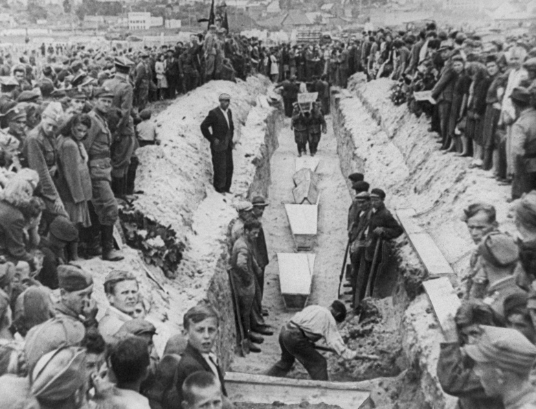 FILE – In this July 1946 file photo mourners crowd around long a narrow trench as coffins of victims of an anti-Semitic massacre are placed in a common grave following mass burial service, in Kielce, Poland. The July 4,1946, massacre killed 42 people, most of them Jews, and wounded over 80. The last known living survivor of the massacre, Joseph Feingold, died from complications from the coronavirus in New York in April. (AP Photo, File)
