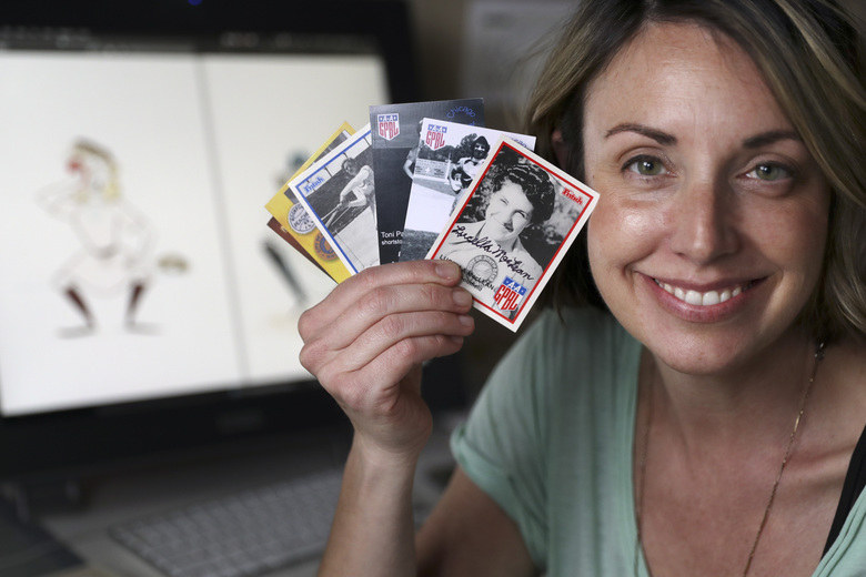 "In this April 30, 2020, photo, Anika Orrock holds some of her autographed baseball cards of players from the All-American Girls Baseball League at her home in Nashville, Tenn. Orrock has written and illustrated a book on the players titled ""The Incredible Women of the All-American Girls Professional Baseball League."" (AP Photo/Mark Humphrey)"