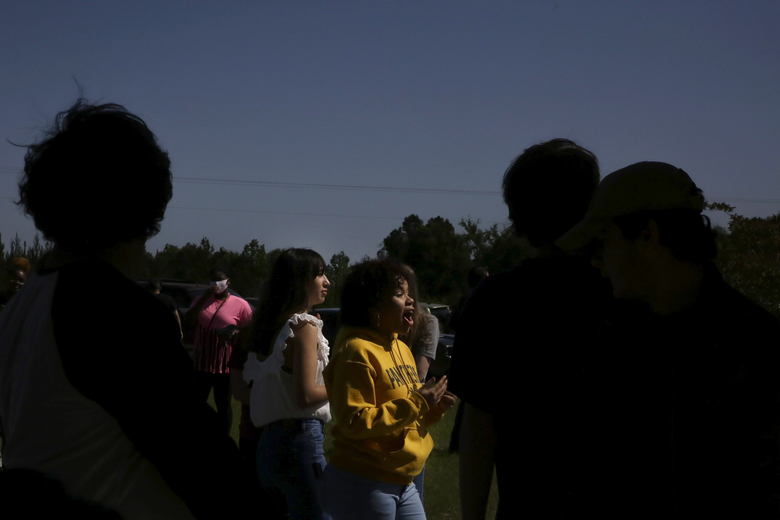 In this Thursday, May 7, 2020 photo, graduating senior, Michelle Pratt stands in line with her classmates for graduation information at Chattahoochee County High School after the school district called an early end to the school year, in Cusseta, Ga. In Georgia, where the school year is ending early for one of every 10 students, many district leaders say the final weeks of the school year would have been dedicated anyway to preparing for and taking standardized tests that are now canceled.  (AP Photo/Brynn Anderson)