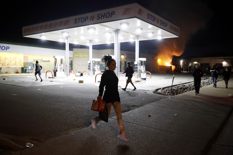 People loot a convenience store Friday, May 29, 2020, in Minneapolis. Protests continued following the death of George Floyd, who died after being restrained by Minneapolis police officers on Memorial Day. (AP Photo/John Minchillo)