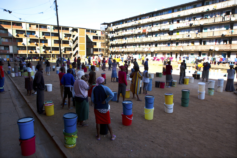 In this April, 24, 2020, photo, people wait to fetch water from a row of communal taps that the group Doctors Without Borders provided in a suburb of Harare, Zimbabwe. For people around the world who are affected by war and poverty, the simple act of washing hands is a luxury, even during the coronavirus pandemic. In Zimbabwe, clean water is often saved for daily tasks like doing dishes and flushing toilets. (AP Photo/Tsvangirayi Mukwazhi)