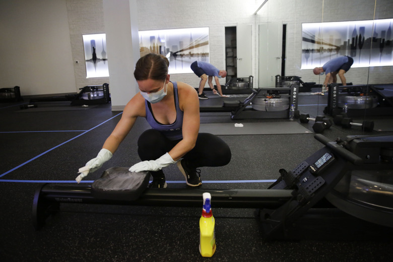 Employee of CITYROW Atlanta Midtown, Ellie Klarl, cleans the equipment after a class as gyms reopen with limited members on Saturday, May 16, 2020, amid the COVID-19 virus in Atlanta.  Big box gyms and local fitness studios are reopening under a patchwork of protocols based on state and local guidance, but most are following some basic protocol.  (AP Photo/Brynn Anderson)