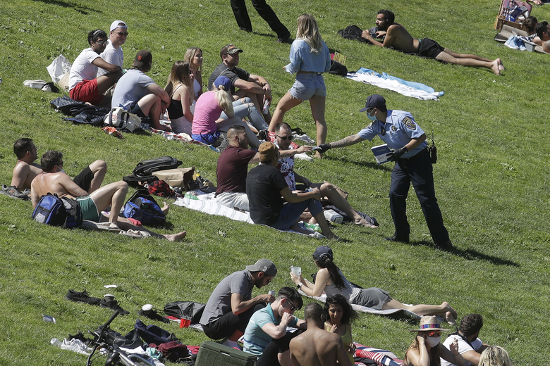 A San Francisco Police cadet hands out face masks to help prevent the spread of the coronavirus, at Dolores Park in San Francisco, Sunday, May 24, 2020. (AP Photo/Jeff Chiu)