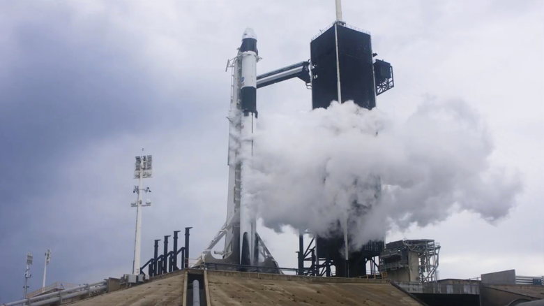 In this Wednesday, May 27, 2020 image from video made available by SpaceX, liquid oxygen vents off the Falcon 9 rocket as NASA astronauts Bob Behnken and Doug Hurley in the Crew Dragon capsule prepare for launch from the Kennedy Space Center in Cape Canaveral, Fla., moments before the mission was aborted due to weather problems. (SpaceX via AP)