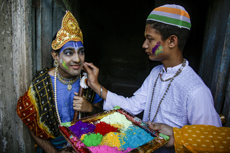 FILE- In this March 7, 2020, file photo, a school boy dressed as Hindu mythological character Krishna has colored powder applied on his face to celebrate the spring festival of Holi, the festival of colors, in Kolkata, India. Seeking comfort in the certainty of the past, Indians are tuning into re-runs of popular Hindu religious dramas, drawing on shared experiences of old times when most questions had answers. Staying home under a lockdown as they wait for the worst of the coronavirus pandemic to pass, millions of Indians are turning to their Gods. Not in their prayer rooms, but on their televisions. (AP Photo/Bikas Das, File)