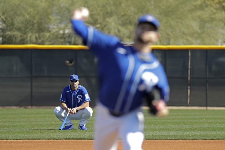 FILE – In this Feb. 16, 2020, file photo, Kansas City Royals manager Mike Matheny, back left, watches as pitcher Jesse Hahn throws during spring training baseball practice in Surprise, Ariz. The Royals had an entire offseason and most of spring training to get to know Mike Matheny. But one unintended consequence of the coronavirus pandemic is they've gotten to know their new manager better than they could ever have imagined. (AP Photo/Charlie Riedel, File)
