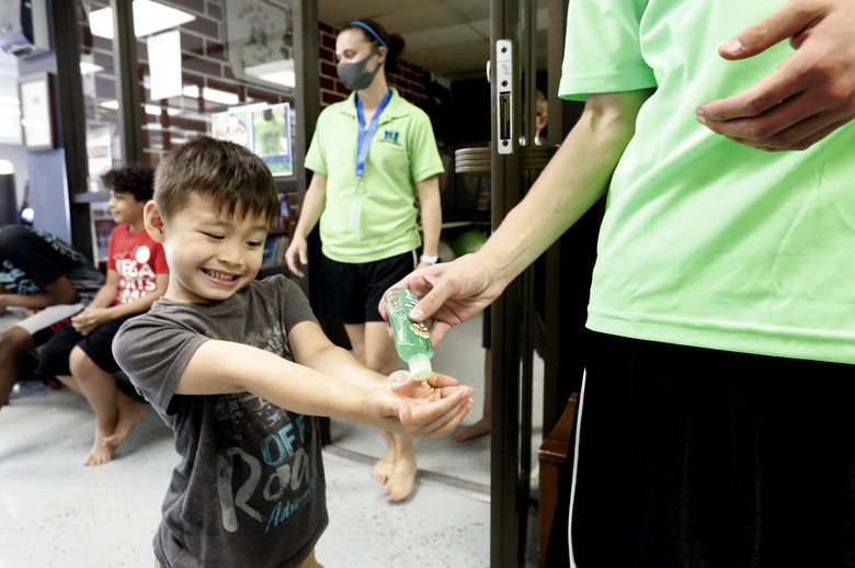 Bruce McCall, 5, smiles as he takes hand sanitizer during martial arts daycare summer camp at Legendary Blackbelt Academy in Richardson, Texas, Tuesday, May 19, 2020. As daycares and youth camps re-open in Texas, operators are following appropriate safety measure to insure kids stay safe from COVID-19. (AP Photo/LM Otero)