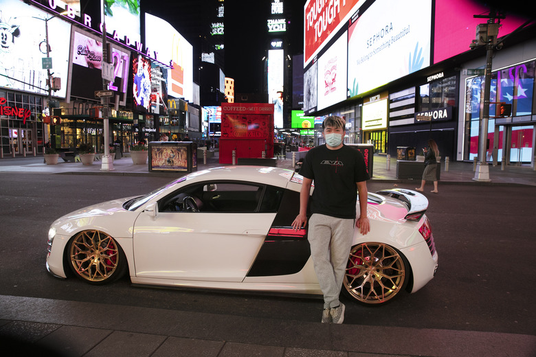 """In this Saturday, May 2, 2020 photo, Danny Lin poses for photos with his 2008 Audi R8 in New York's Times Square during the coronavirus pandemic. """"I never bring my car here,"""" said the 24-year-old from Queens. """"Only for today, to get some cool shots."""" (AP Photo/Mark Lennihan)"""