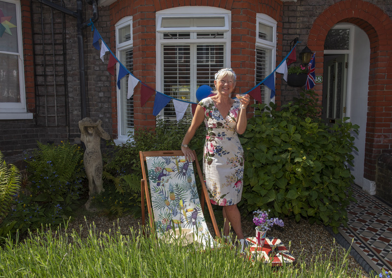 Jo Banks drinks a shandy in her front garden decorated with bunting and a Union Jack during Victory in Europe Day celebrations in Berkhamsted, England, Friday, May 8, 2020. (AP Photo/Elizabeth Dalziel)