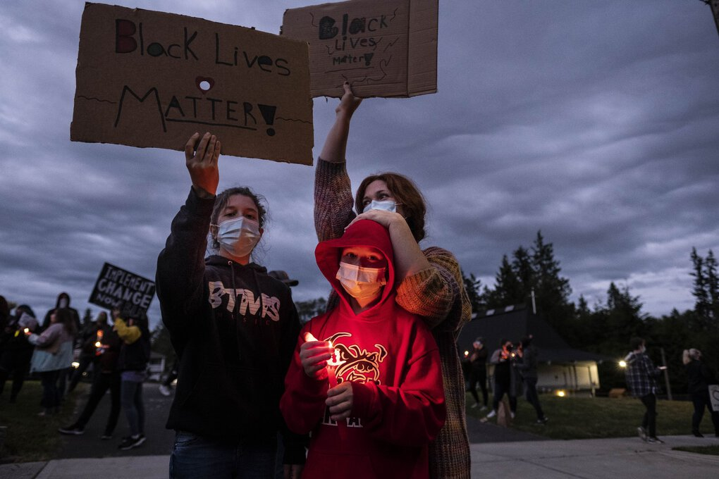Kate Berg and her children Clementine, 12, and August, 10, came from their home in Mountlake Terrace to join a candlelight vigil Wednesday for  George Floyd in Edmonds. (Dean Rutz / The Seattle Times)