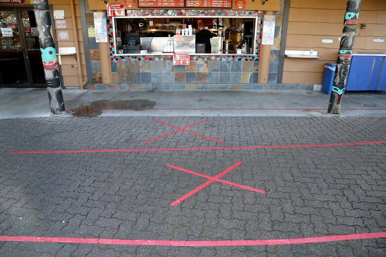 At Ivar's fish bar under the Ship Canal Bridge, red tape on the pavement reminds people coming to take out orders that social distancing is still important. However, Ivar's will be reopening under the modified Phase 1 that King County has been cleared to participate in.  (Greg Gilbert / The Seattle Times)
