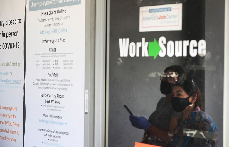 Estella Flores, right, and Maria Mora, left, are reflected in a window as they look for information in front of the closed California State Employment Development Department on Thursday, May 14, 2020 in Canoga Park, Calif. (Brian van der Brug/Los Angeles Times/TNS) 1668043 1668043