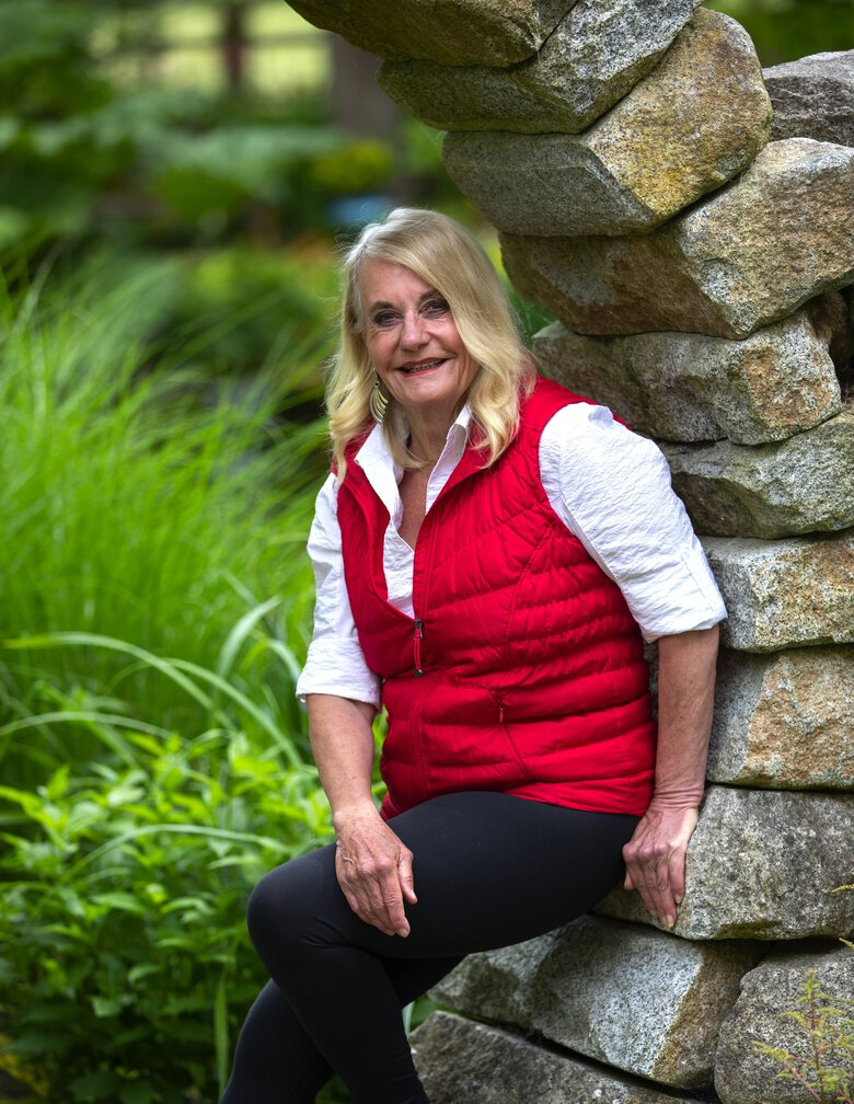 Joanne White poses inside the gate near the entrance to her garden   in Redmond. (Mike Siegel / The Seattle Times)
