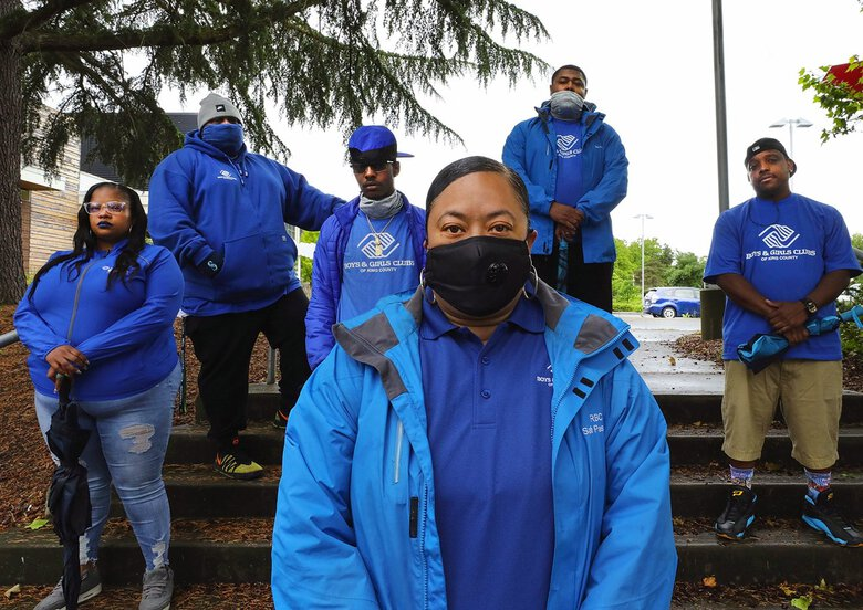 """Marty Patu-Jackson, front, head of Safe Passage, works to ensure safety in Rainier Beach without police. Team members behind her are Ricole Jones, left, Leonard Johnson, Mario Sellers, D'Mario Mallory and Jonathan Ramirez. """"We weren't depending on law enforcement,"""" Patu-Jackson said of a South End demonstration last Sunday. """"We were depending on each other."""" (Alan Berner / The Seattle Times)"""