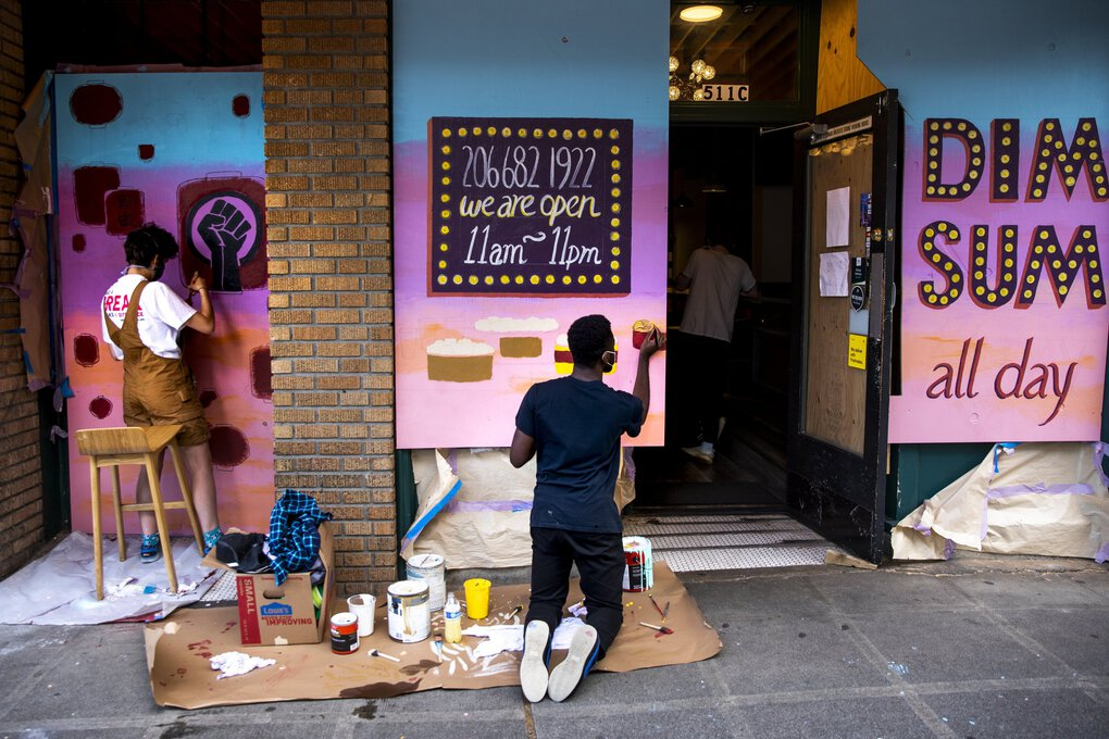 Mina Carroll, left, and Jean-Marc Lubiba paint a social justice and Dim Sum mural on the Hong Kong Bistro during the #4BLM Community Art Walk  Sunday.  (Bettina Hansen / The Seattle Times)