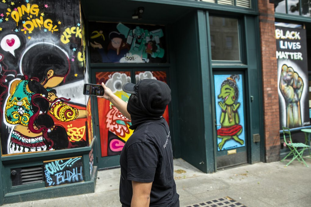 "Miko Pugal narrates video of the murals as he walks through the Chinatown International District. ""We shouldn't just show up for people being murdered. We should be showing up for people's humanity,"" he said. The boarded-up shops in the Chinatown International District are filled with murals during the #4BLM Community Art Walk on Sunday. Community members came up with the murals as a way to beautify and protect the historic neighborhood. (Bettina Hansen / The Seattle Times)"