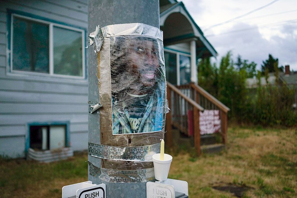 A photo of Manuel Ellis, who died in police custody in March, is taped to a pole at a makeshift memorial in Tacoma. (Ruth Fremson / The New York Times)