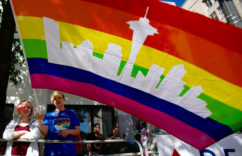 Kes Sorensen, 17, and Sean Robertson, 16, wave a Seattle-themed pride flag as they wait for the parade to start at Westlake Park in 2016.  (Sy Bean / The Seattle Times)