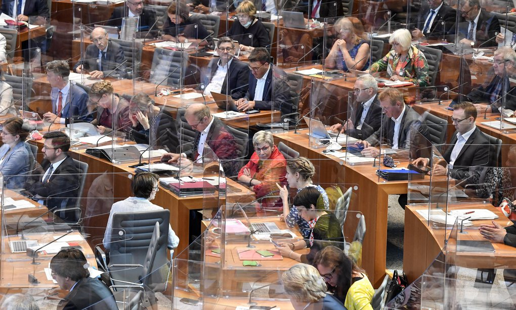 Lawmakers attend a session of the state parliament of the German state of North Rhine-Westphalia in Duesseldorf, Germany, on Wednesday. Plastic partitions were set up at lawmakers' desks due to the coronavirus. (Martin Meissner / The Associated Press)