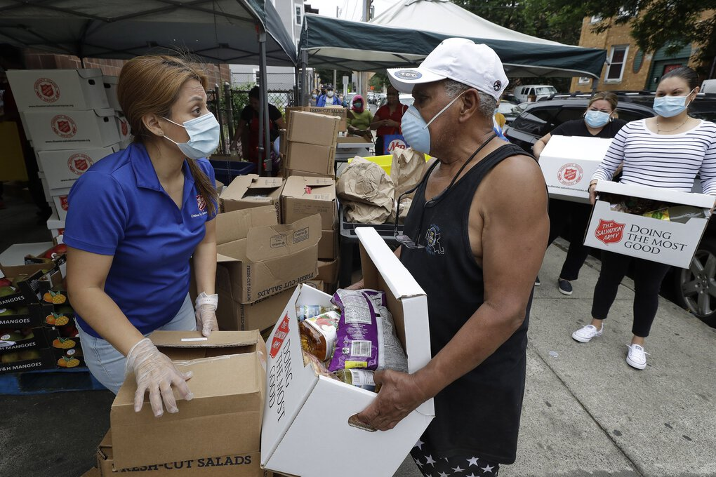 Salvation Army worker Brenda Gonzalez, of Saugus, Mass., left, distributes food to an unidentified man while others impacted by the coronavirus wait in line at a Salvation Army center on Tuesday, in Chelsea, Mass. (Steven Senne / The Associated Press)