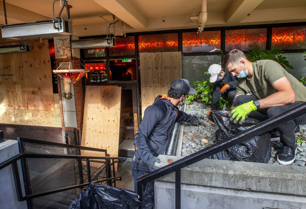 Volunteers clean up broken glass and other damage outside the Cheesecake Factory at Bellevue Square after looting broke out Sunday in the Eastside city. (Mike Siegel / The Seattle Times)