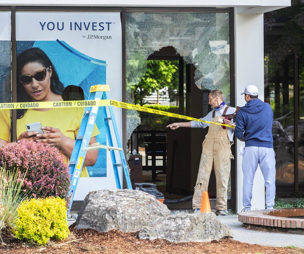 Workers survey damage to a Chase Bank on Northeast Eighth Street in downtown Bellevue on Monday after protesters turned destructive in that city on Sunday. (Mike Siegel / The Seattle Times)