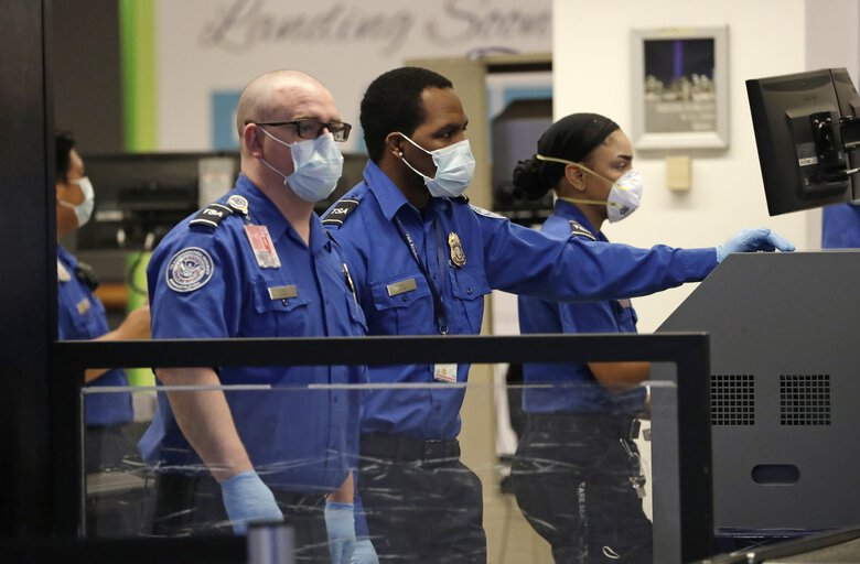 In this photo taken May 18, 2020, TSA officers wear masks as they work at a security check point at Seattle-Tacoma International Airport. The coronavirus pandemic has brought changes to security policy, and more changes may still be yet to come. (Elaine Thompson / The Associated Press)