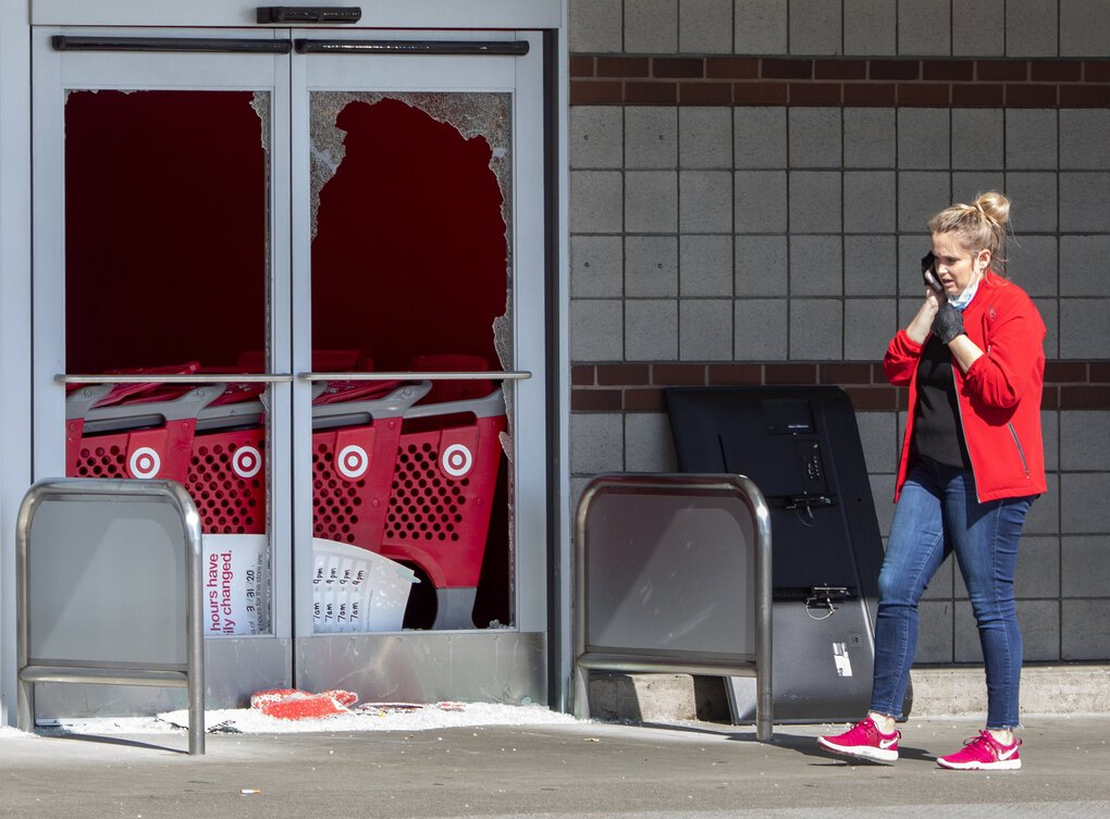 A employee talks on the phone in front of the Target store in Tukwila, which suffered damage when looters struck the area around Southcenter mall on Sunday night. One worker said it might be days before the store would reopen.  (Ellen M. Banner / The Seattle Times)