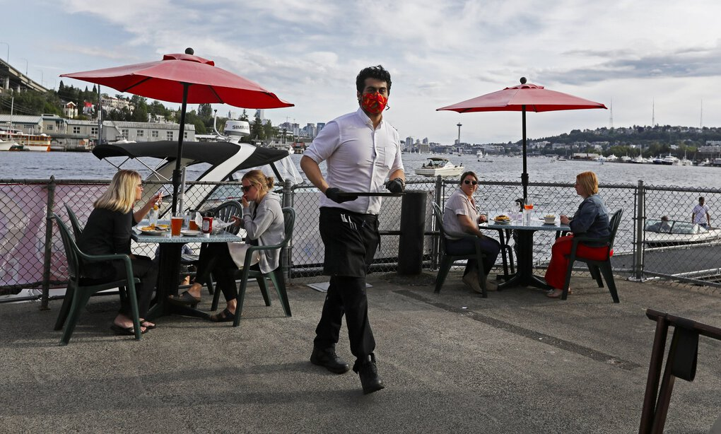Jonathan Martinez, center, a server at Ivar's Salmon House on north Lake Union, walks past socially distanced guests Wednesday. The restaurant reopened Monday at reduced capacity, and the staff  hasundergone COVID-19 prevention training. (Ken Lambert / The Seattle Times)