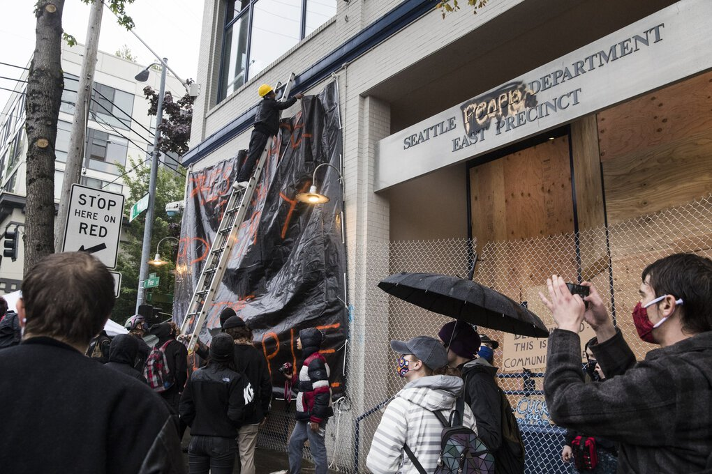 "Anthony Bar straps in a new sign on the East Precinct on Tuesday that says ""This space is now property of the Seattle people."" (Amanda Snyder / The Seattle Times)"