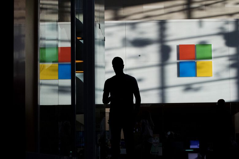 A shopper passes in front of a Microsoft store in Toronto last year. (Brent Lewin / Bloomberg)