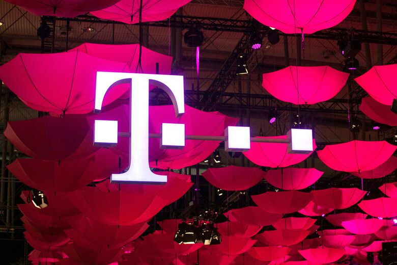 The T-Mobile logo is seen suspended from the ceiling along with a collection of coloured umbrellas. (Bloomberg)